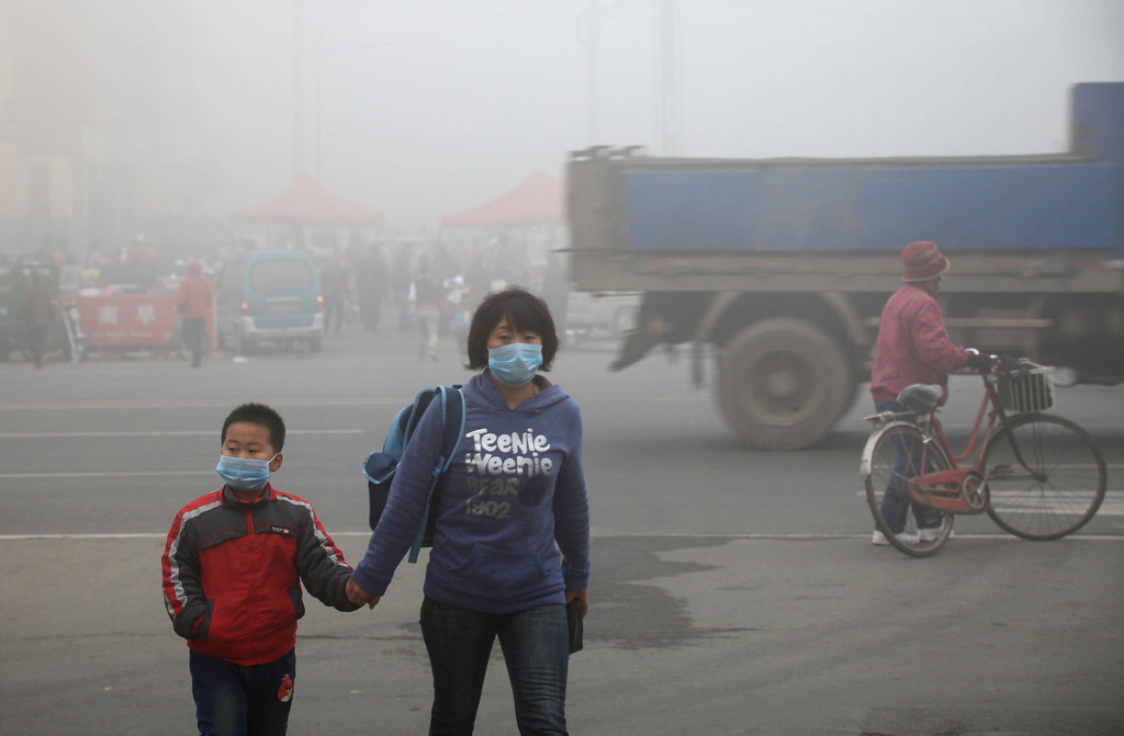 A woman walks with her child on a street as schools were closed due to the heavy smog in Jilin, northeast China's Jilin province on October 22, 2013. AFP PHOTOSTR/AFP/Getty Images